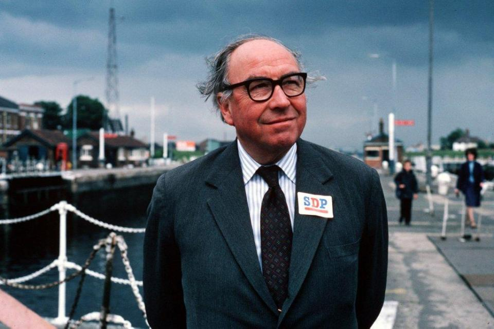Image shows Roy Jenkins standing beside a canal. His thinning hair blown by a breeze, his jacket lapel bearing a sticker with the letters SDP