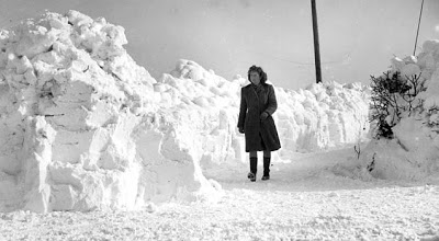 Black and white image of woman walking between high snow drifts