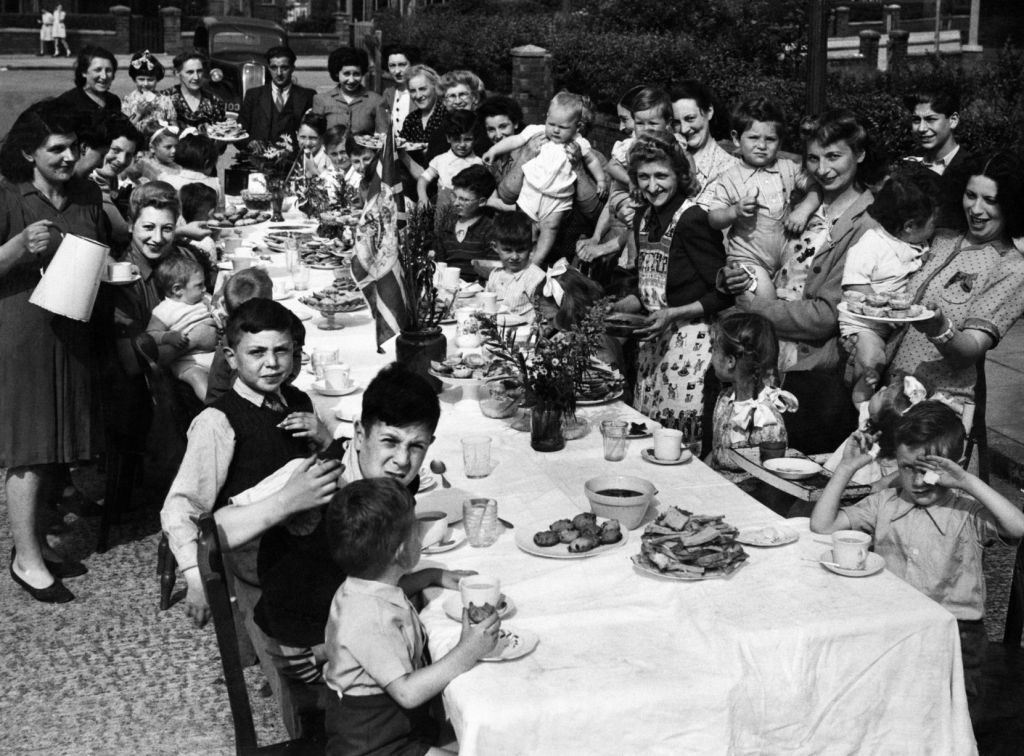 Children seated at a long table being served by happy adults most of whom are female and in 1940s garb.