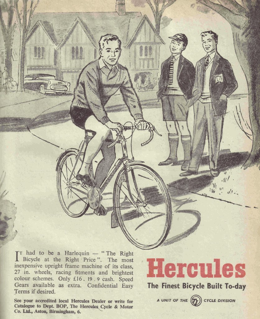 Two schoolboys look on as a fellow rides a bicycle with dropped handlebars.