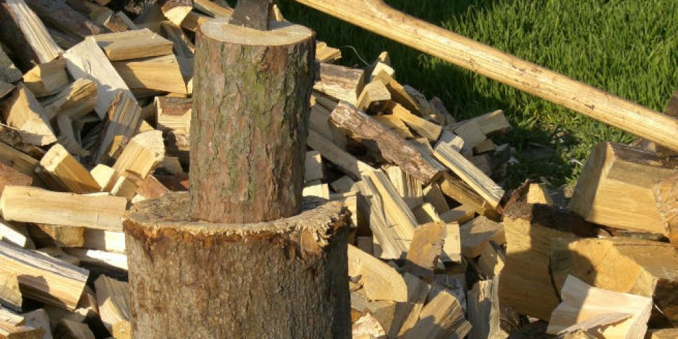 Image depicts a small log upright on top of a larger log. An axe is embedded in the top of the small log. Split logs are scattered all around.
